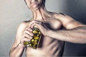 Hombre abriendo con esfuerzo un tarro de conserva