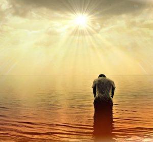 Hombre contemplando al sol mientras medita