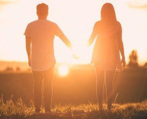 Contacto corporal hombre y mujer frente a la puesta de sol