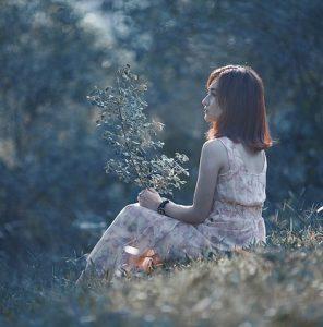Mujer en la naturaleza abriendo su cuerpo a la comunicacion intrapersonal